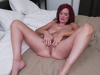 Redhead mommy Andi James rubs her pussy