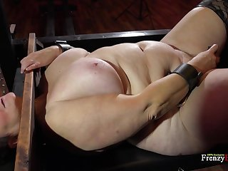 BBW bitch is locked in the pillory and she's ready to do whatever she's told