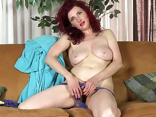 Red haired housewife, Zinnia Blue is using a black dildo while masturbating on the sofa