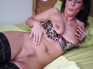 Tattoed mature dark haired MILF Candy exposes her small tits