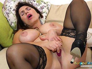 Solo horny mature Josephine on her sofa masturbates with her vibrating toy